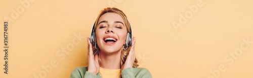 panoramic shot of happy girl listening music in wireless headphones with closed eyes on yellow background