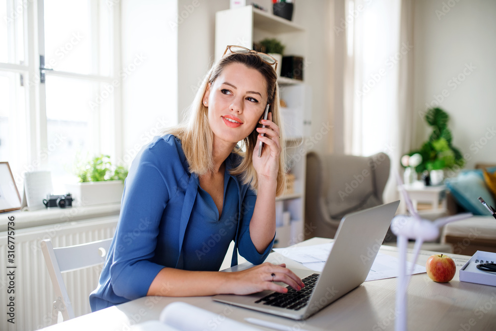 Fototapeta Young woman architect sitting at the desk indoors in home office, working.