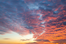 Sunset Fire In The Sky Of Natural Color. Dark Blue Clouds With Red Reflections Of The Setting Sun. Scenic Cloudscape At Sundown.