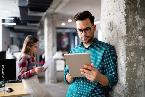 Cuadros en Lienzo Young man using technology, digital tablet in corporate business office