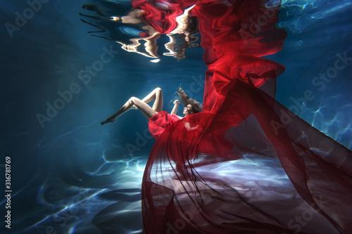 Obraz Underwater scene. A woman, a fashion model in the water in a beautiful dress swims like a fish. - fototapety do salonu
