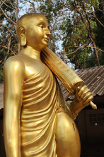 Statue Of Walking Buddha In Traditional Theravada Style With Umbrella In The Buddhist Temple.