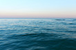 Wide horizon of sea and sky. Sunset seascape. Calm open sea ocean. Sunset evening time. Soft focus, motion blur.