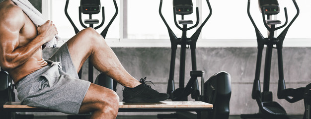 Fitness man with dumbbell tired and resting in gym