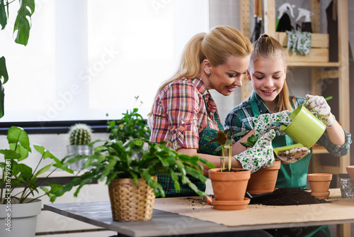 Mother and daughter repotting plants together at home garden Fototapete