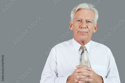Fotografie, Tablou Portrait of senior businessman with hands clasped over gray background
