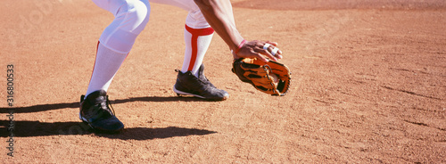 Photo Low section of baseball catcher in position on field