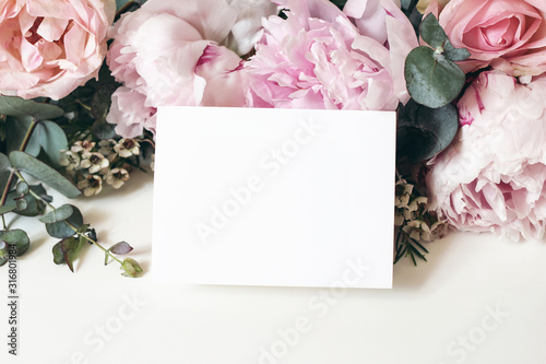Obraz Wedding, birthday stationery mock-up scene. Blank greeting card, invitation. Decorative floral composition. Closeup of pink roses petals, peonies, hydrangea flowers, eucalyptus on white table. - fototapety do salonu