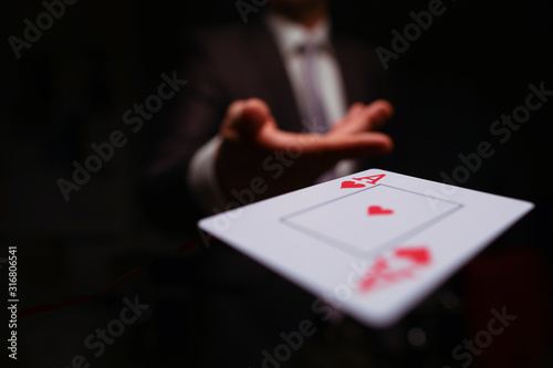 Close-up of man in presentable suit throwing playing card ace of hearts to opponent on dark background Canvas Print