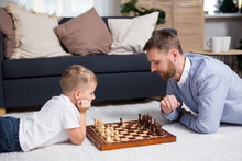 Father And Son Lying On Floor At Home And Playing Chess
