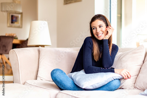 Obraz Relaxed woman sitting on comfortable sofa at home - fototapety do salonu
