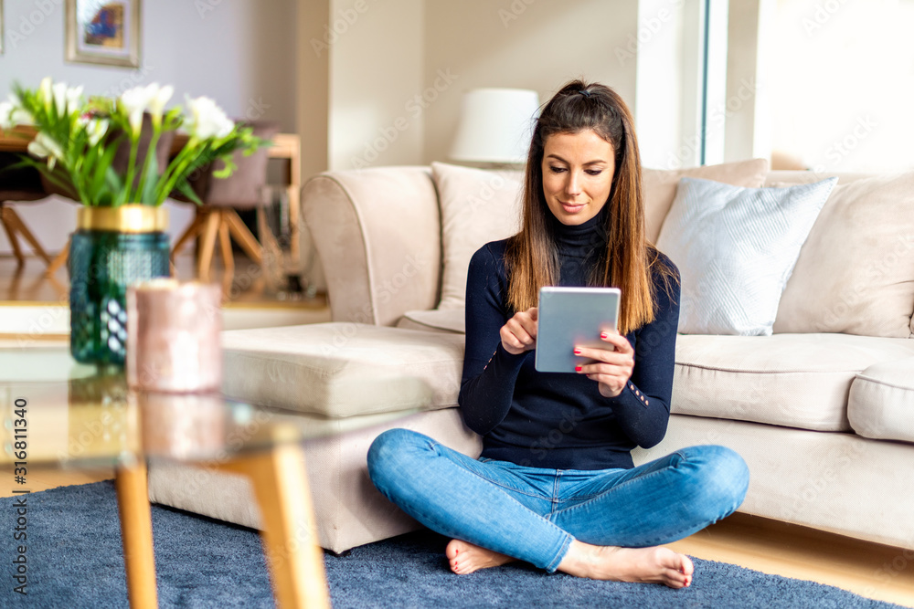 Fototapeta Attractive woman with digital tablet relaxing at home