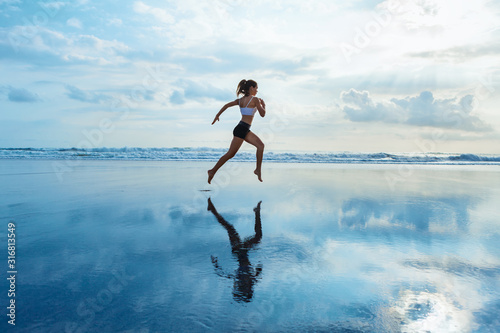 Fototapeta Barefoot young girl with slim body running along sea surf by water pool to keep fit and burning fat. Beach background with blue sky. Woman fitness, jogging sports activity on summer family vacation. obraz