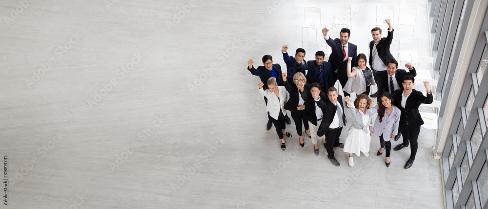 Fototapeta Top view of group of multiethnic business people celebrating and .happy success positive teamwork with hands up. Victory successful, celebrate achievement and acquisitions concept. Aerial view.