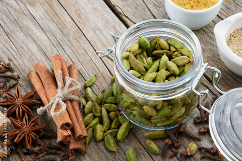 Fototapeta Jar of whole green cardamom pods and spices - cinnamon sticks, cardamom, allspices and anise on wooden table. Ayurveda treatments. obraz