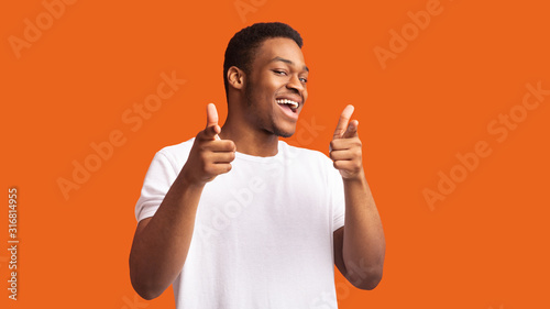 Fotomural Happy afro guy choosing you over orange background