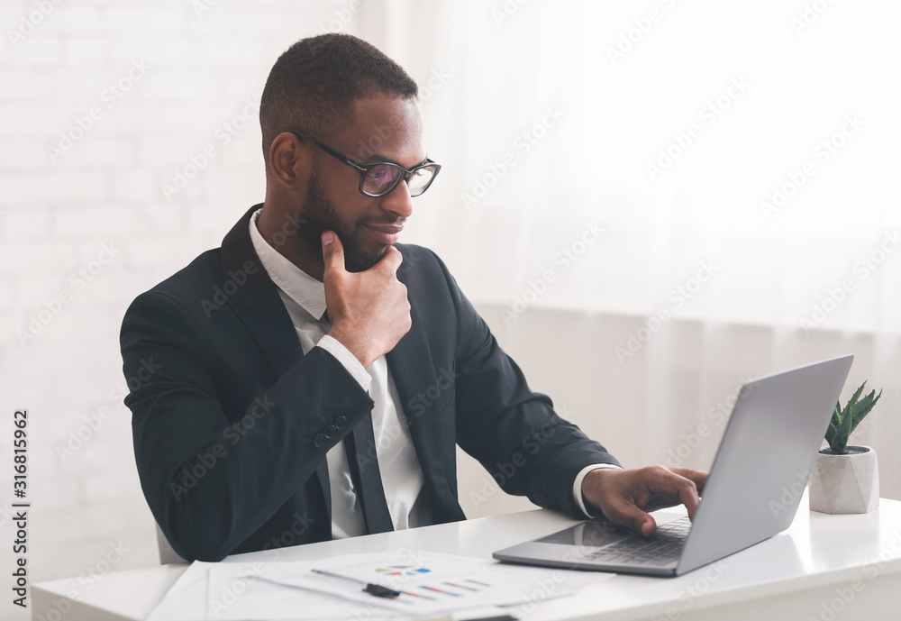 Fototapeta Concentrated afro businessman looking at laptop screen