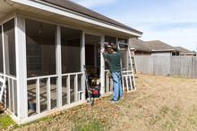 Homeowner Works On Repairing D...