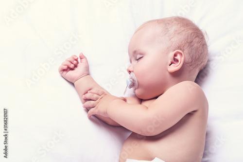 Beautiful little boy with soother sleeping on bed at home Tapéta, Fotótapéta