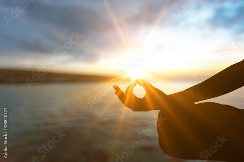 Human silhouette meditating at sunset background