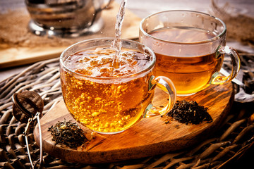 two cups of black tea on a wicker table early in the morning. Tea morning at dawn. The process of pouring tea.