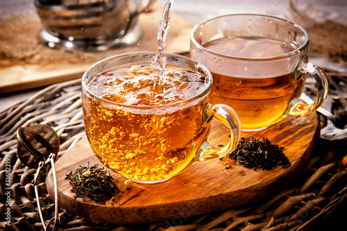 Obraz two cups of black tea on a wicker table early in the morning. Tea morning at dawn. The process of pouring tea. - fototapety do salonu