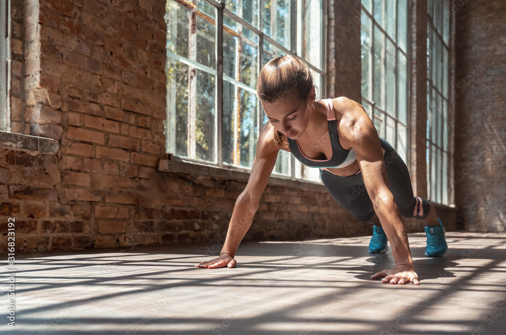 Fototapeta Young fit sporty active woman wear sportswear standing in plank pose doing yoga fitness training workout stretching core push up exercise on wooden floor in modern sunny gym space indoors, pushups