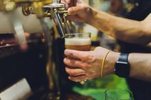 Bartender Pours Beer Into Glas...
