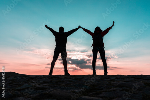 Photo Couple silhouette with raised arms holding hands and looking at sunset