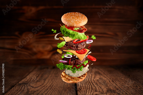 Fotomural Maxi hamburger, double cheeseburger with flying ingredients isolated on wooden background