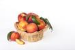 Leinwanddruck Bild Fresh peaches in basket on white wooden table