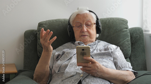 Old woman is listening music (old hits) on a smartphone. Wallpaper Mural