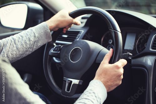 Man holding steering wheel and driving his car Canvas Print