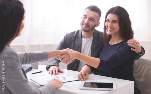 Insurance broker handshaking with young couple of clients