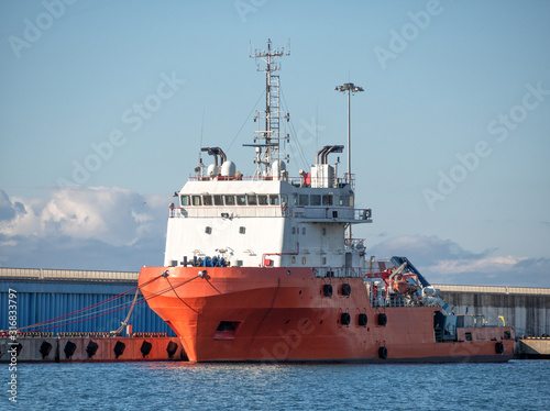 Photo Platform supply vessel anchored in sea port at sunny day