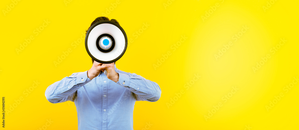 Fototapeta man with a megaphone over yellow background, panoramic image with space for text, announcement concept