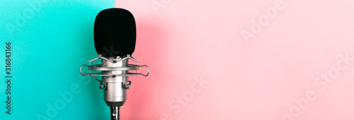 Obraz na plátně studio microphone on a blue pink background, panoramic mock-up with space for te