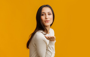 Beautiful brunette girl blowing kiss at camera, posing over yellow background