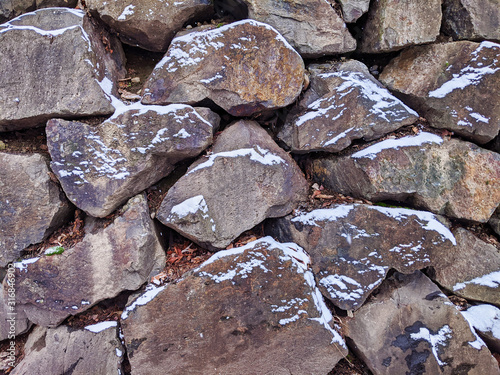 view of a rock wall, dusted with snow after a winter storm Fototapet