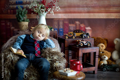 Obraz na plátně Sweet toddler boy, fall asleep on little baby couch while reading book at home