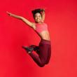Leinwanddruck Bild - Carefree athletic girl in sportswear happily jumping up