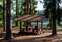 Resting Place With Roof Shelter And Picnic Table In The Forest, Between Trees. River Baltoji Ancia In The Background. Sunny Day And Calm, Peaceful Atmosphere.