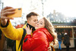 young romantic couple in love making selfie on smartphone, man kissing in cheek his girlfriend, having fun together and looking happy. Spending time together in the city, having a date. urban romantic