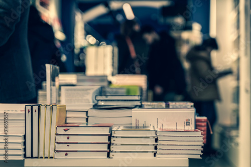 Pile of books, abstract blurred background in book store or in library Tableau sur Toile