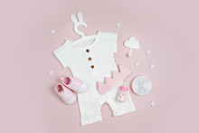 Set Of Baby Clothes And Accessories On Pink Background. White Bodysuit On Cute Hanger With Bunny Ears And Baby Shoes, Cotton Crown And Toys. Fashion Newborn Clothes. Flat Lay, Top View