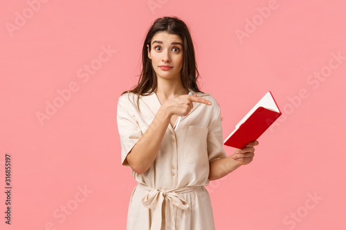 Fototapeta Did you wrote this. Intrigued brunette girl asking question about something written in notebook, pointing finger at note and looking puzzled, standing pink background confused obraz na płótnie