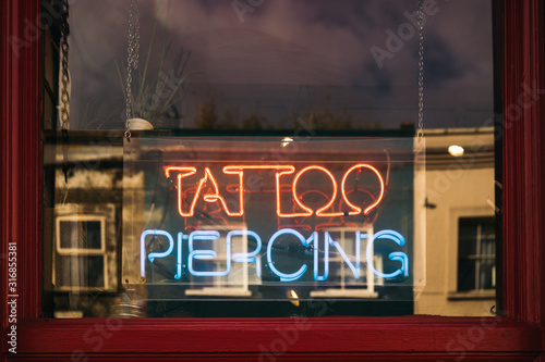 Photo Neon sign in the window of a tattoo parlor in New York City