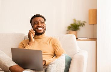 Happy Black Man Talking On Cellphone Working On Laptop Indoor