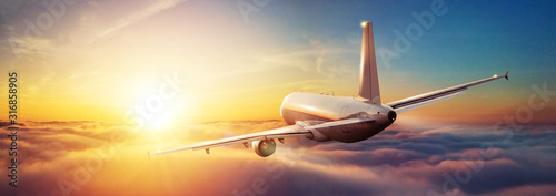 Passengers commercial airplane flying above clouds - 316858905