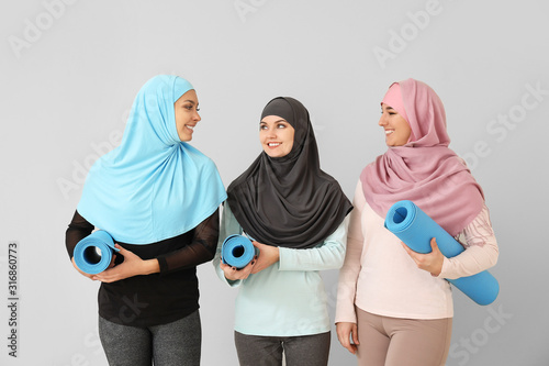 Sporty Muslim women with yoga mats on light background Slika na platnu